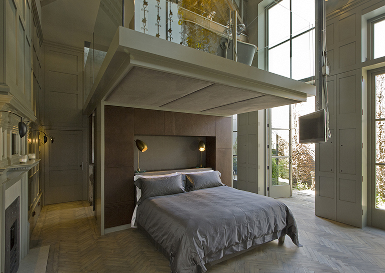 Master bedroom in the old coach house reuses the original parquet floor from the old workshop and has double height shuttered windows onto a walled garden. The TV can be winched up to the mezzanine to watch movies in the bath above.