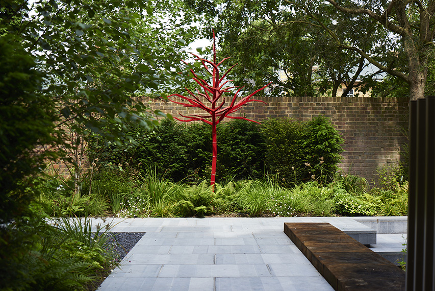 A metal tree sculture by Jivko Sedlarski is silhouetted against the yew hedge.