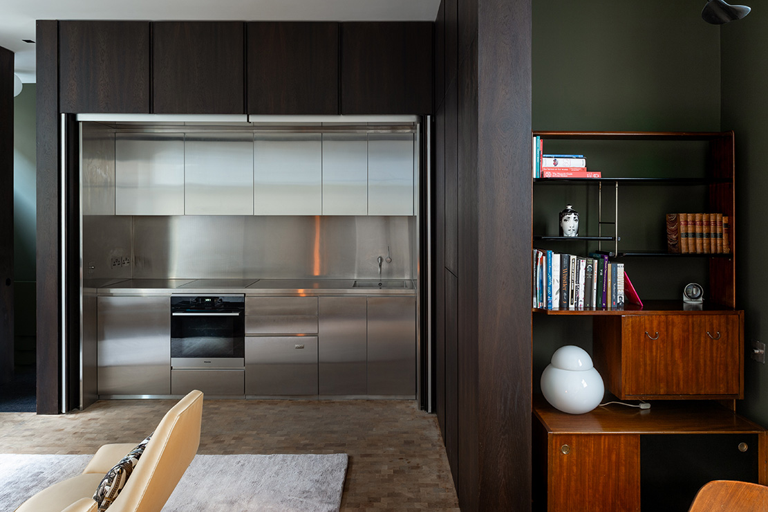 The steel kitchen can be hidden from the living space with bi-folding timber panels.
