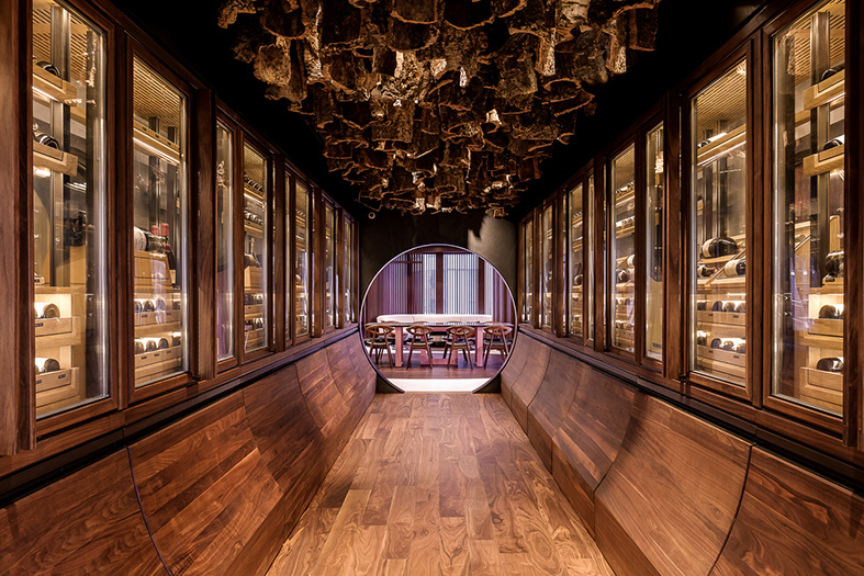 The climatically controlled cabinets of the cellar have been detailed in timber with curved wine display drawers below and a ceiling hung with raw bark from cork trees.