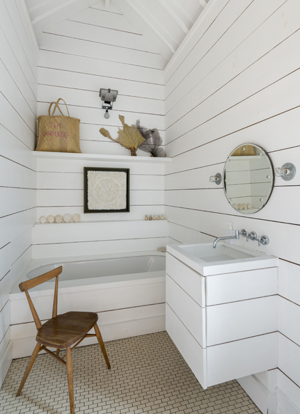 The bathroom is clad in white painted timber boards.