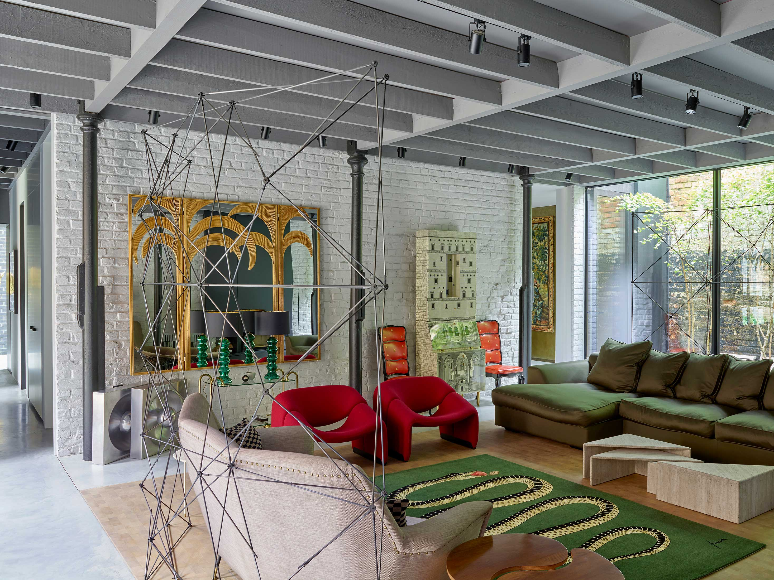 Living room with raftered ceiling and original cast iron columns salvaged from the stables flanked on two sides by minimal sliding glass walls onto cobbled courtyards.