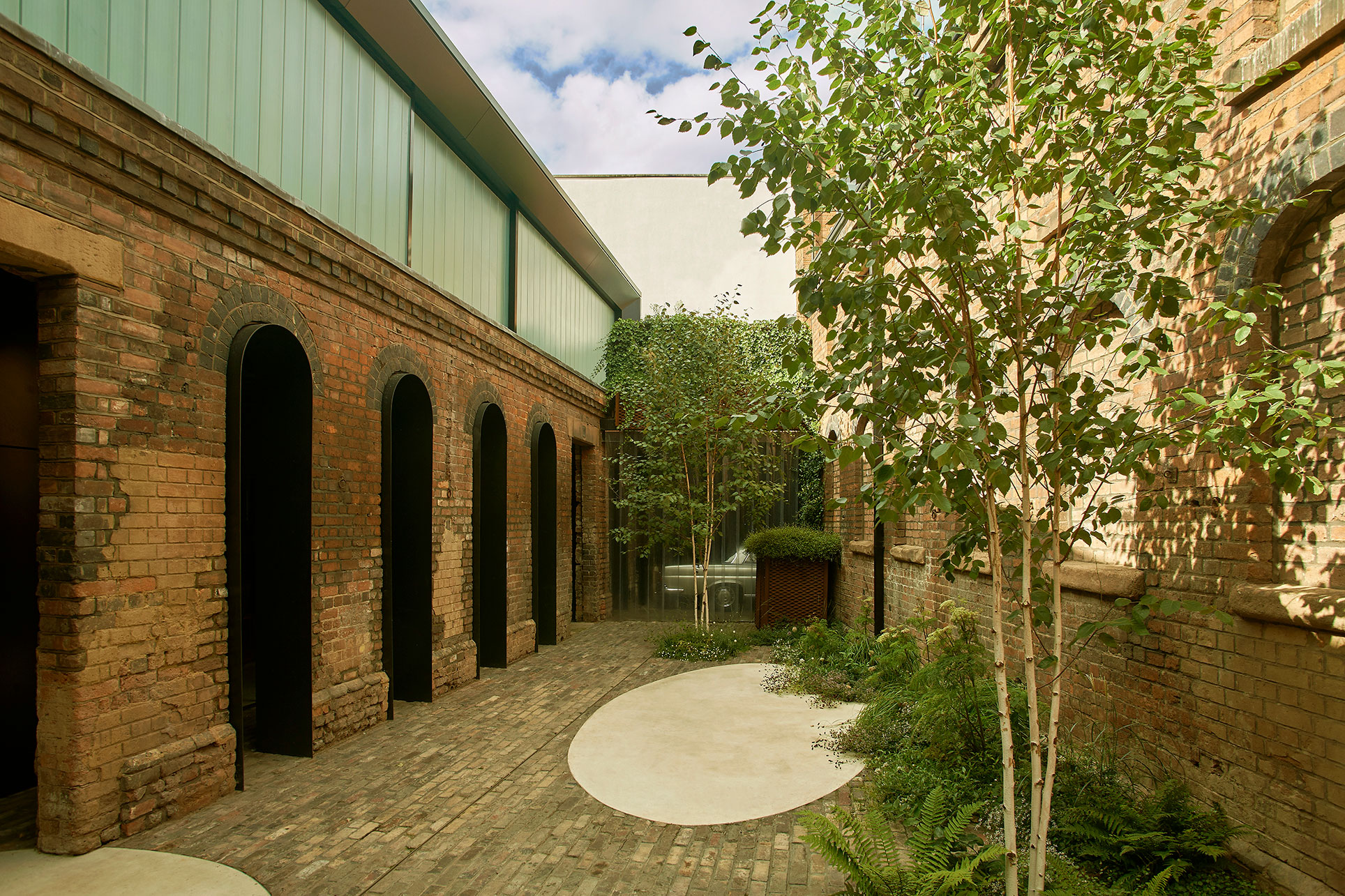 Original brickwork openings have been lined in rolled steel to provide an arcaded podium onto the main cobbled courtyard.  This contrasts with lightness of the cast glass and steel monolith of the first floor.