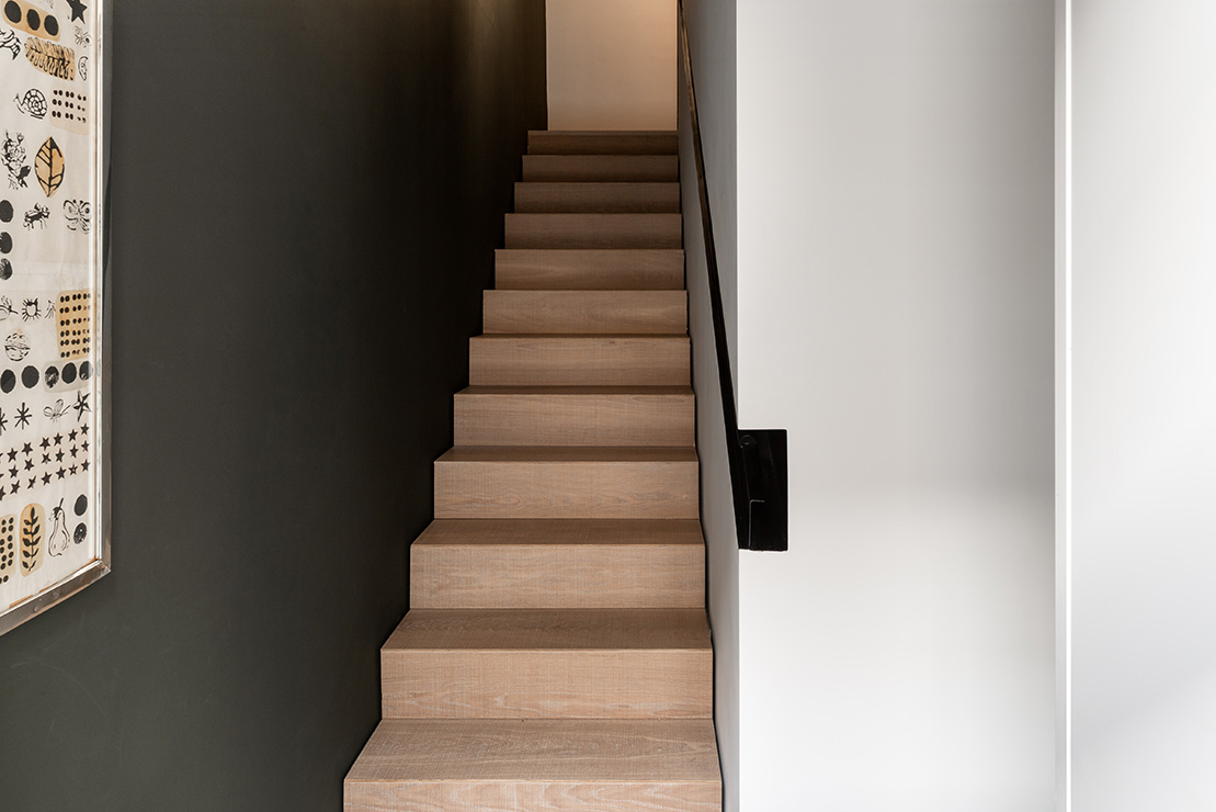 A timber stair with a recessed handrail leads up to the bedrooms.