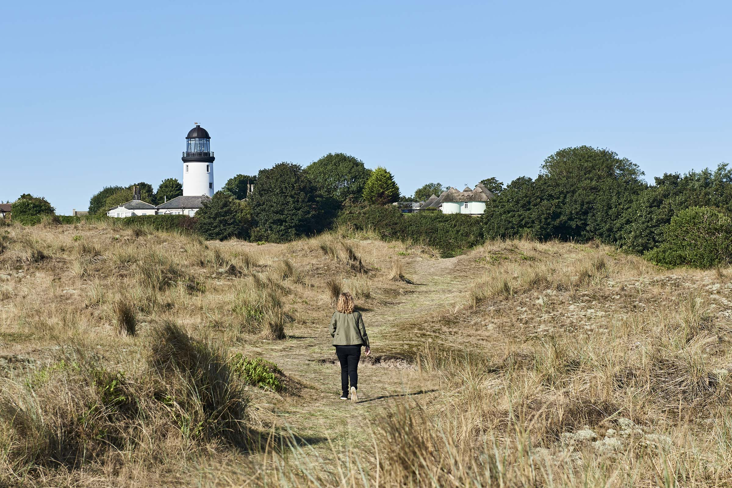 The restored Lighthouse is set back from the shoreline across the sand dunes.